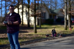 A man wearing plaid flies a drone.
