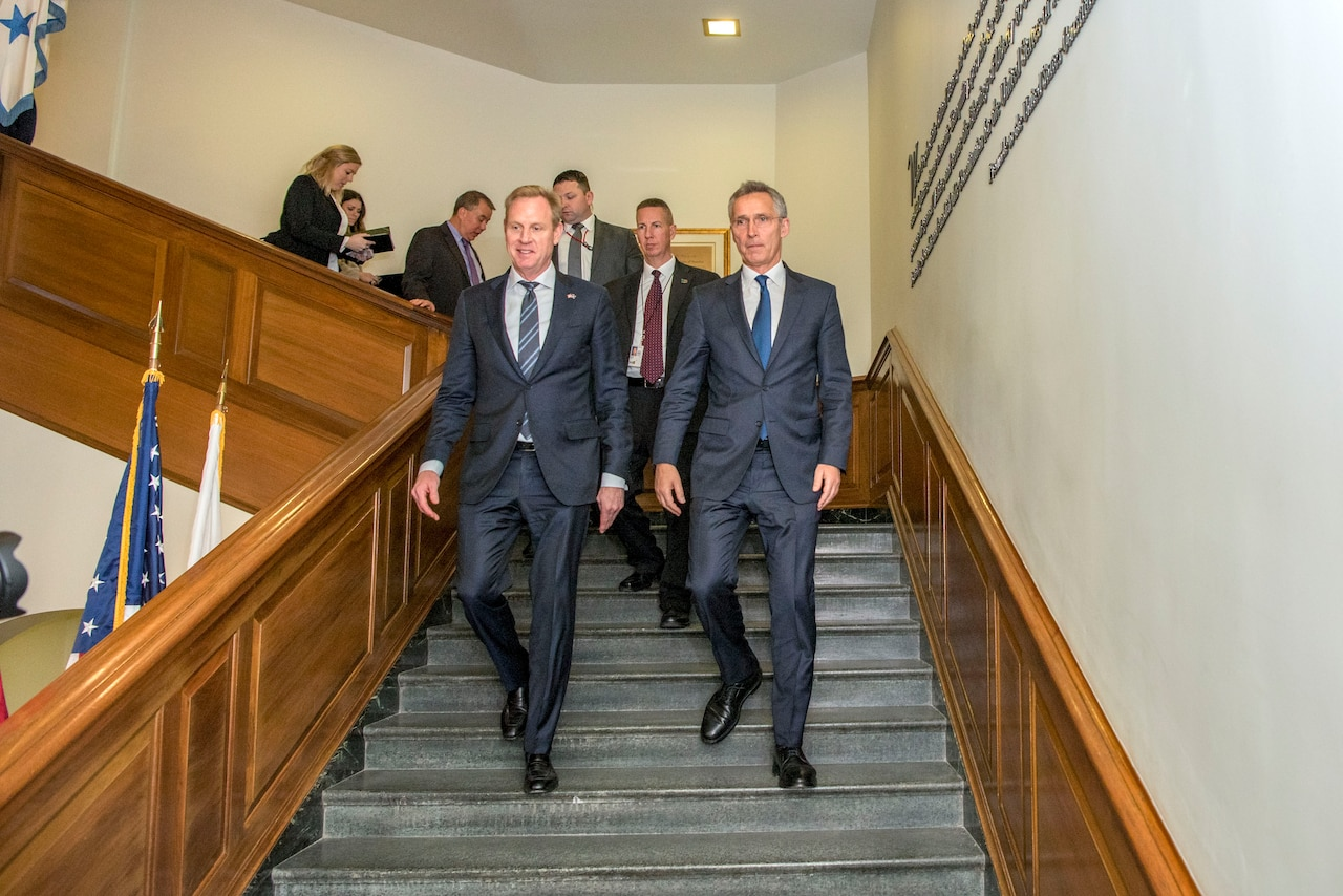 Acting defense secretary and NATO secretary general walk down stairs at the Pentagon.