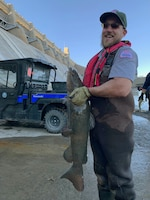 JOHN MARTIN RESERVOIR, Colo. -- USACE park ranger Christopher Gauger displays a flathead catfish while transferring it to the hatchery truck to be relocated in the reservoir upstream, Nov. 1, 2018.