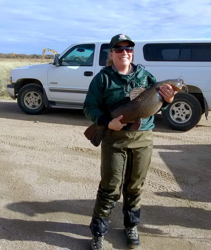 JOHN MARTIN RESERVOIR, Colo. -- USACE park ranger Valerie Thompson holds one of the fish salvaged from the stilling basin before it is transferred to the main reservoir, Nov. 1, 2018.