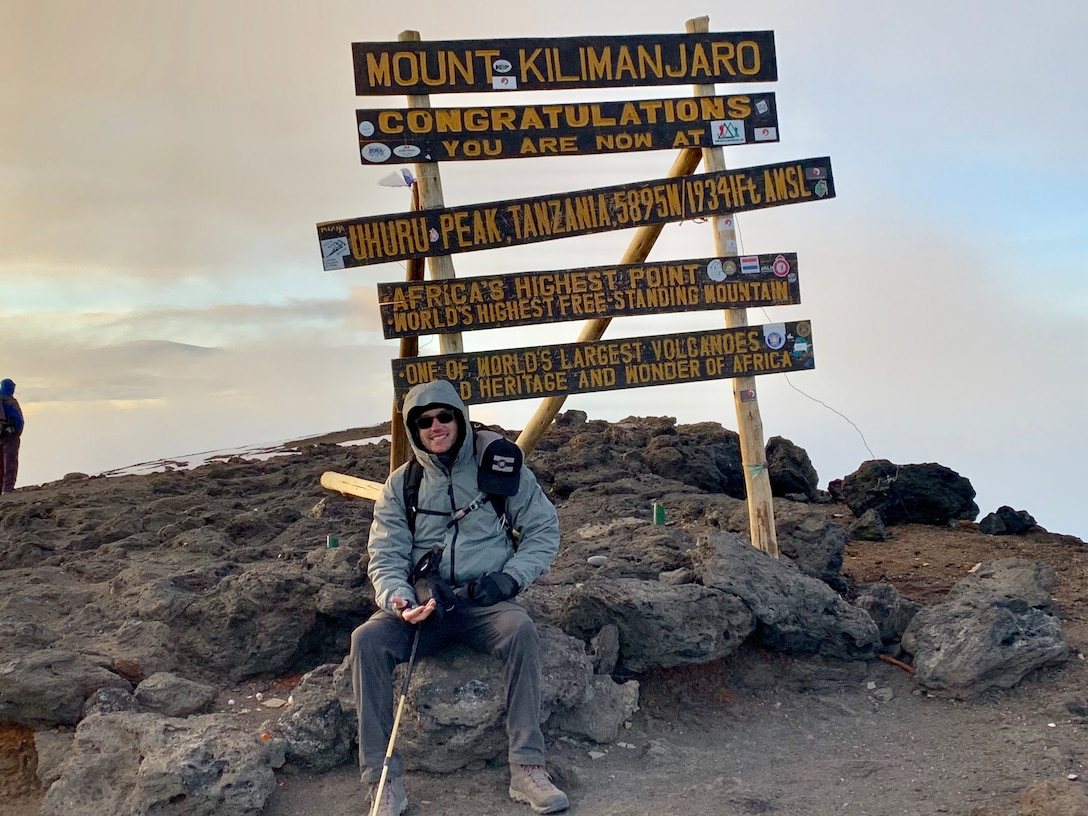 Jeff Crow, material planner in the Defense Logistics Agency Troop Support's Industrial Hardware supply chain, rests on a rock under the sign that marks his accomplishment in climbing Tanzania's Mount Kilimanjaro during a trip in December 2018.