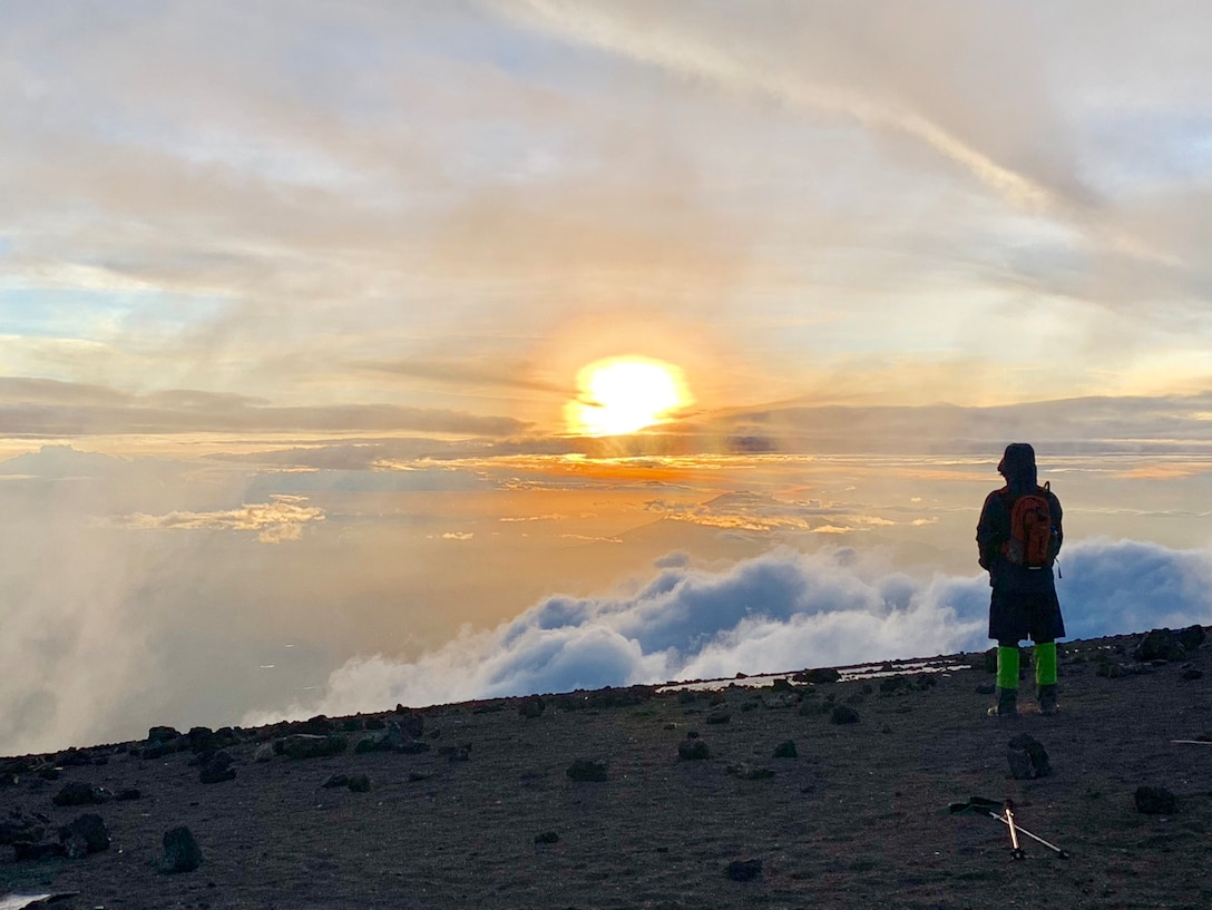 Jeff Crow, material planner in the Defense Logistics Agency Troop Support's Industrial Hardware supply chain, stands atop Tanzania's Mount Kilimanjaro, watching the sunset from above the clouds during a trip in December 2018.