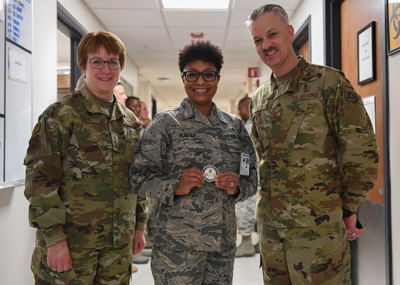 U.S. Air Force Lt. Gen. Dorothy A. Hogg, Air Force Surgeon General, and Chief Master Sgt. G. Steve Cum, Medical Enlisted Force and Enlisted Corps chief, present a coin to Master Sgt. Teronda L. Hunter, 633rd Dental Squadron clinical flight chief, at Joint Base Langley-Eustis, Virginia, Jan. 9, 2019.