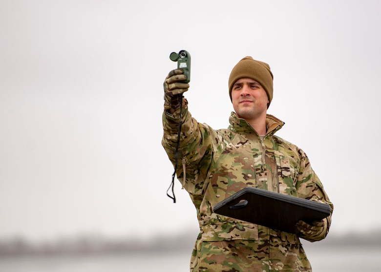 Senior Airman Aaron Cathey, 436th Operations Support Squadron weather forecaster, uses a handheld weather-monitoring device to gather meteorological information Jan. 24, 2019, on Dover Air Force Base, Delaware. Checks using the handheld device are taken from the same location to ensure consistency. (U.S. Air Force photo by Staff Sgt. Jared Duhon)