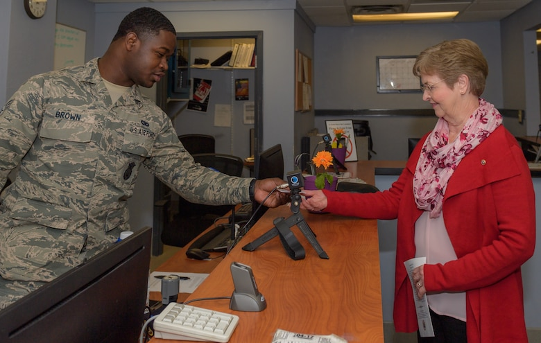 U.S. Air Force Senior Airman Leonard Brown, 81st Security Forces visitors center clerk, provides a Gold Star Family Member ID card to Ann Hamilton, sister of Staff Sgt. James W. Davis, inside the visitor center at Keesler Air Force Base, Mississippi, Jan. 24, 2019. Davis was killed in 1968 while conducting military operations in Vietnam . (U.S. Air Force photo by Andre' Askew)