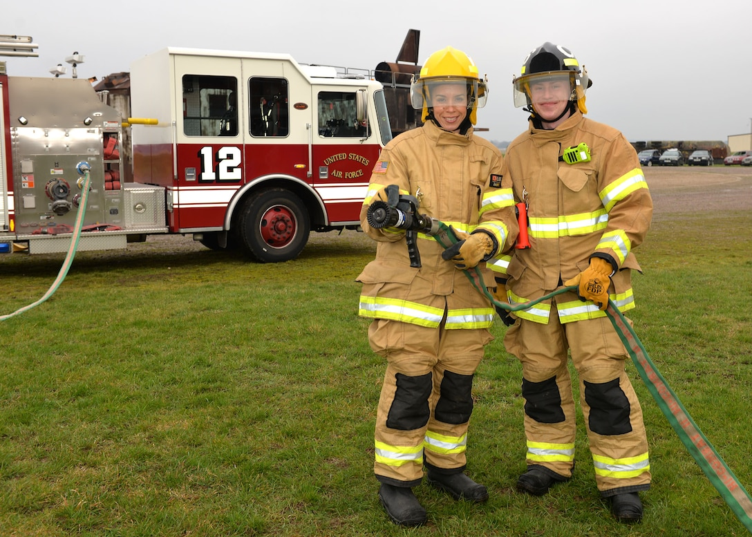 U.S. Air Force Chief Master Sgt. Kristina Rogers, left, 100th Air Refueling Wing command chief, poses for a photo with Airman 1st Class Adam Strizak, 100th Civil Engineer Squadron firefighter, before participating in Class A structural live-fire training at RAF Mildenhall, England, Jan. 24, 2019. The 100th ARW command chief participated in the training, performed semi-annually, to get an idea of what the RAF Mildenhall firefighters go through to keep up-to-date in their fundamental skills. Class A training burns combustibles such as wood and paper, and is one of the most realistic forms of live-fire training conducted. (U.S. Air Force photo by Karen Abeyasekere)