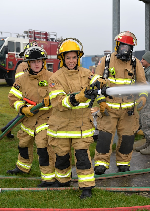 U.S. Air Force Chief Master Sgt. Kristina Rogers, 100th Air Refueling Wing command chief, uses the fire hose with assistance from Airman 1st Class Adam Strizak, left, 100th Civil Engineer Squadron firefighter, and Lead Firefighter Simon Evans, 100th CES Fire Department crew manager, during Class A structural live-fire training at RAF Mildenhall, England, Jan. 24, 2019. The 100th ARW command chief participated in the training, performed semi-annually, to get an idea of what the RAF Mildenhall firefighters go through to keep up-to-date in their fundamental skills. Class A training burns combustibles such as wood and paper, and is one of the most realistic forms of live-fire training conducted. (U.S. Air Force photo by Karen Abeyasekere)