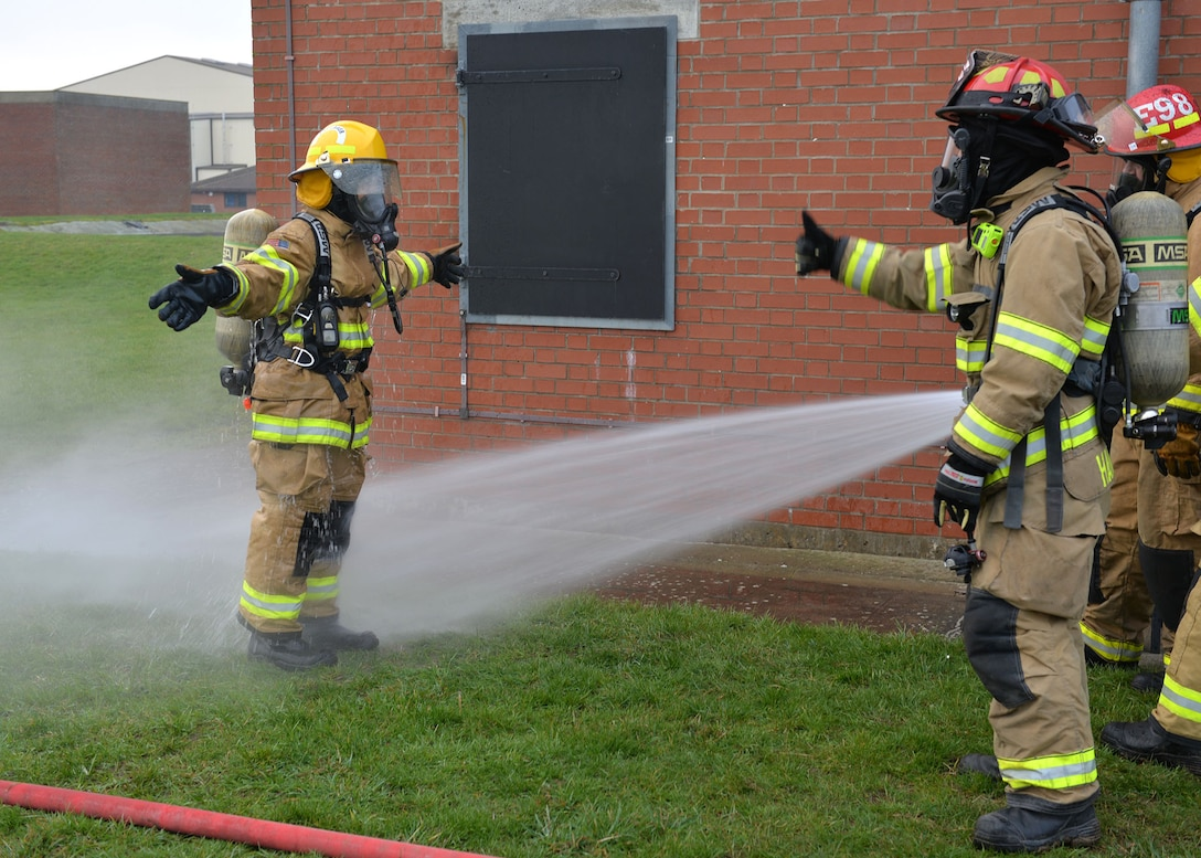 Firefighters from the 100th Civil Engineer Squadron Fire Department hose down U.S. Air Force Chief Master Sgt. Kristina Rogers, 100th Air Refueling Wing command chief, as part of the decontamination process after she participated in Class A structural live-fire training at RAF Mildenhall, England, Jan. 24, 2019. The 100th ARW command chief participated in the training, performed semi-annually, to get an idea of what the RAF Mildenhall firefighters go through to keep up-to-date in their fundamental skills. Class A training burns combustibles such as wood and paper, and is one of the most realistic forms of live-fire training conducted. (U.S. Air Force photo by Karen Abeyasekere)