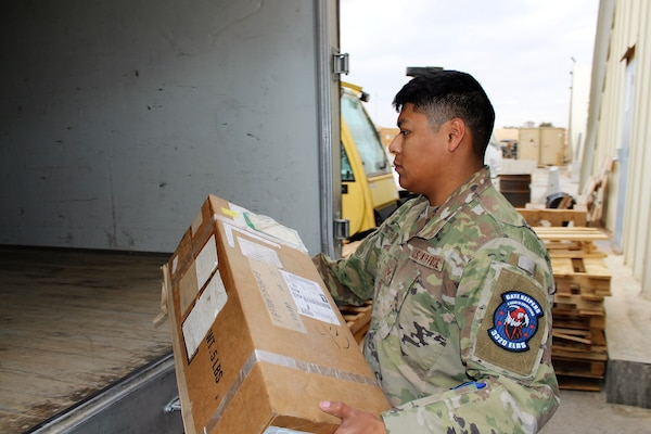 ":  SOUTHWEST ASIA – Senior Airman Andrew Fabian, 332nd Air Expeditionary Wing, 332nd Expeditionary Logistics Readiness Squadron vehicle operator, loads packages onto a delivery truck at an undisclosed location, January 19.  The 332 ELRS ground transportation team performs several delivery ""sweeps"" each day, picking up and delivering personnel and cargo to and from all the main warehouses, supply shops and aircraft. (US Air Force photo by Maj. John T. Stamm)"