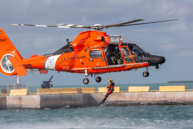 A Coast Guard Air Station Miami rescue swimmer jumps out of a MH-65D Dolphin helicopter to assist 514th Air Mobility Wing Reserve Citizen Airmen during water survival training at Naval Air Station Key West's Truman Harbor, Key West, Fla., Nov. 16, 2018.
