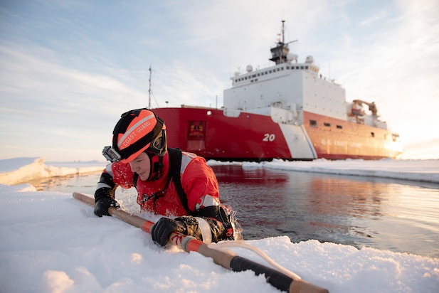 U.S. Coast Guard Petty Officer 3rd Class Shannon Eubanks pulls herself out from the Arctic Ocean during ice rescue training Wednesday, Oct. 3, 2018