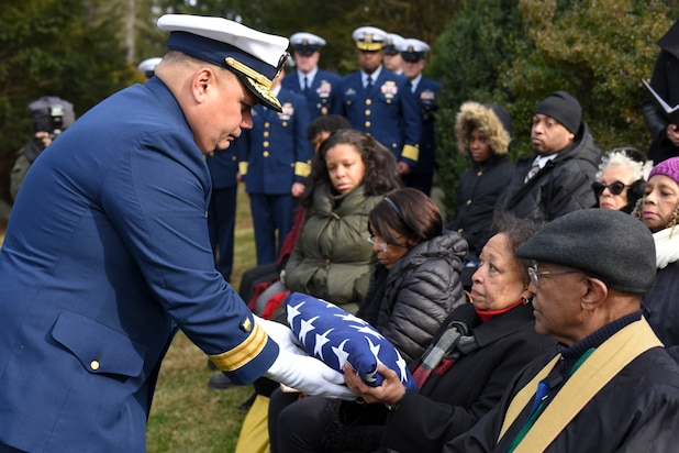 Rear Adm. Andrew Tiongson, commander First Coast Guard District, passes a folded American flag to a family member during funeral services for Dr. Olivia Hooker in White Plains, New York, Dec. 5, 2018. Dr. Hooker was the first African-American woman to enlist in the Coast Guard. (U.S. Coast Guard photo by Petty Officer 3rd Class Steve Strohmaier)