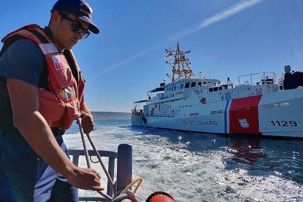 Fireman Patrick Saragoza ties off a fender aboard a Coast Guard Station San Diego 45-foot Response Boat-Medium during a joint patrol with the Coast Guard Cutter Forrest Rednour off the coast of Southern California Nov. 27, 2018