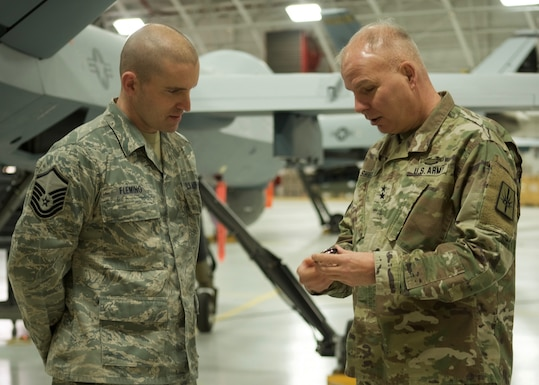 Master Sgt. James Fleming, assigned to the 174th Attack Wing, New York Air National Guard, receives a challenge coin from Major General Ray Shields, the Adjutant General of New York, during Shield's visit to Hancock Field Air National Guard Base, Syracuse, N.Y. on January 16, 2019.Challenge coins are presented by general officers to mark excellent work and accomplishment. (U.S. Air National Guard photo by Tech Sgt. Barbara Olney)