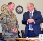 Army Col. Matthew Voyles, Medical supply chain director, left, talks with Dr. David Bobb, DHA pharmacy operations division chief, right, at DLA Troop Support in Philadelphia Jan. 24, 2019.