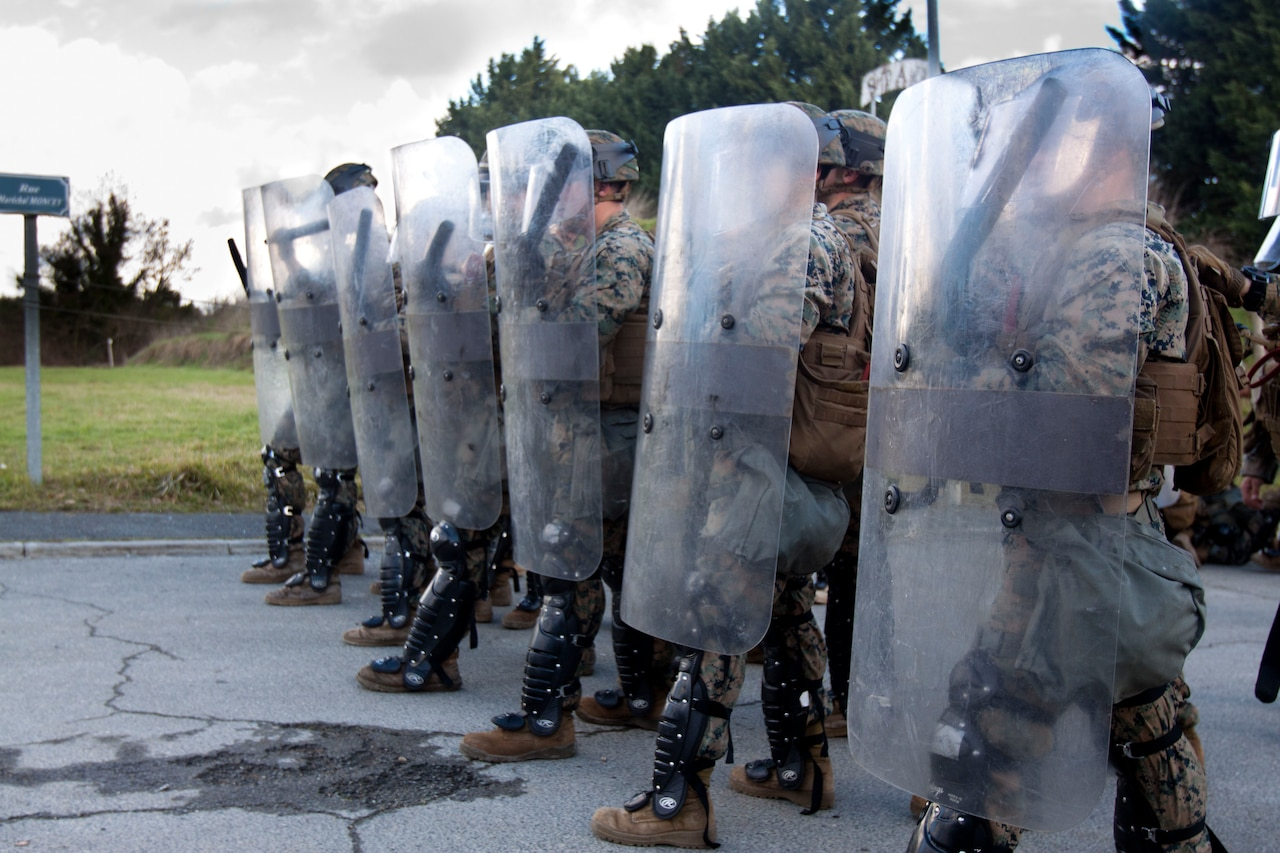 Marines stand in a line holding riot shields.