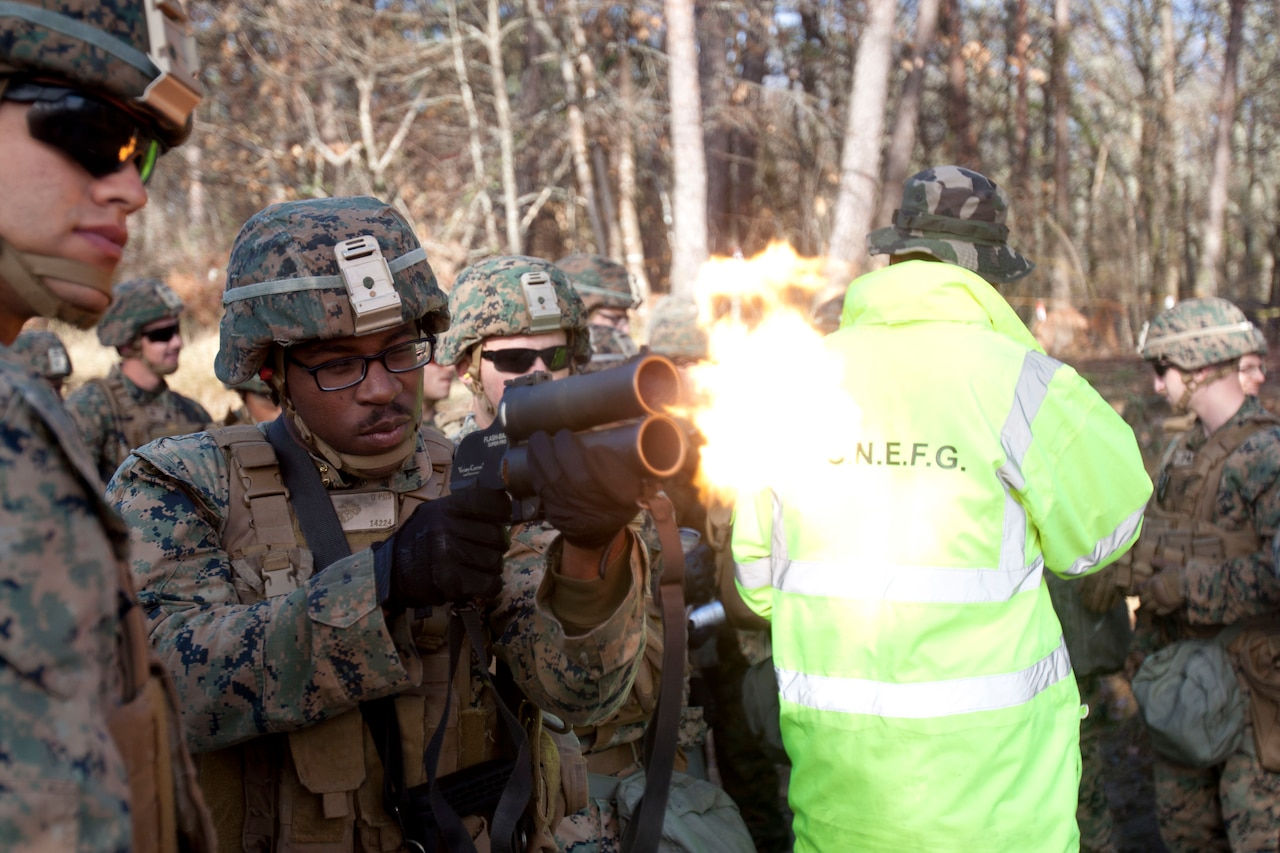 A Marine fires a small weapon, which emits a burst of flame.