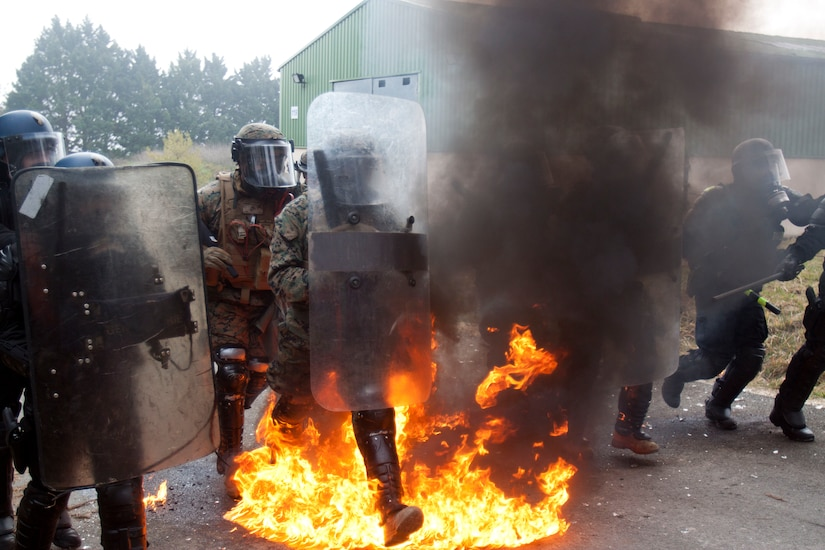 Marines and French gendarmes wearing riot control gear run through flames.