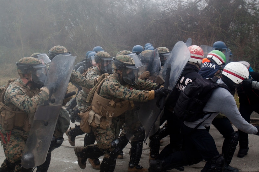 Marines and French gendarmes with riot shields push a line of role playing protestors.