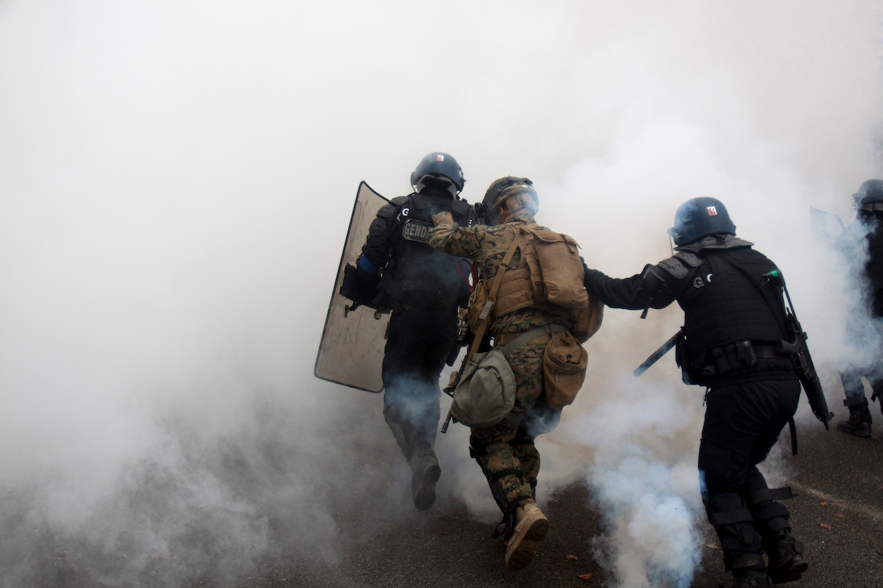 Marines and French gendarmerie in riot control gear run through a cloud of smoke.
