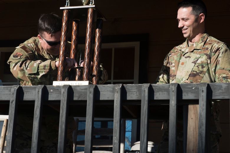 U.S. Air Force Lt. Col. Travis Norton, 25th Attack Group commander, left, puts his squadron patch on a trophy, symbolizing defeat, while Maj. Darryl Hebert, 20th Force Support Squadron commander smiles, at Skeet and Trap range, Shaw Air Force Base, S.C., Jan. 25.