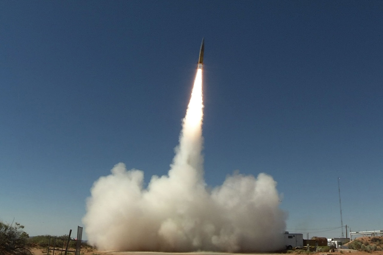 A missile launches skyward during a daytime test, leaving a trail of smoke and fire.