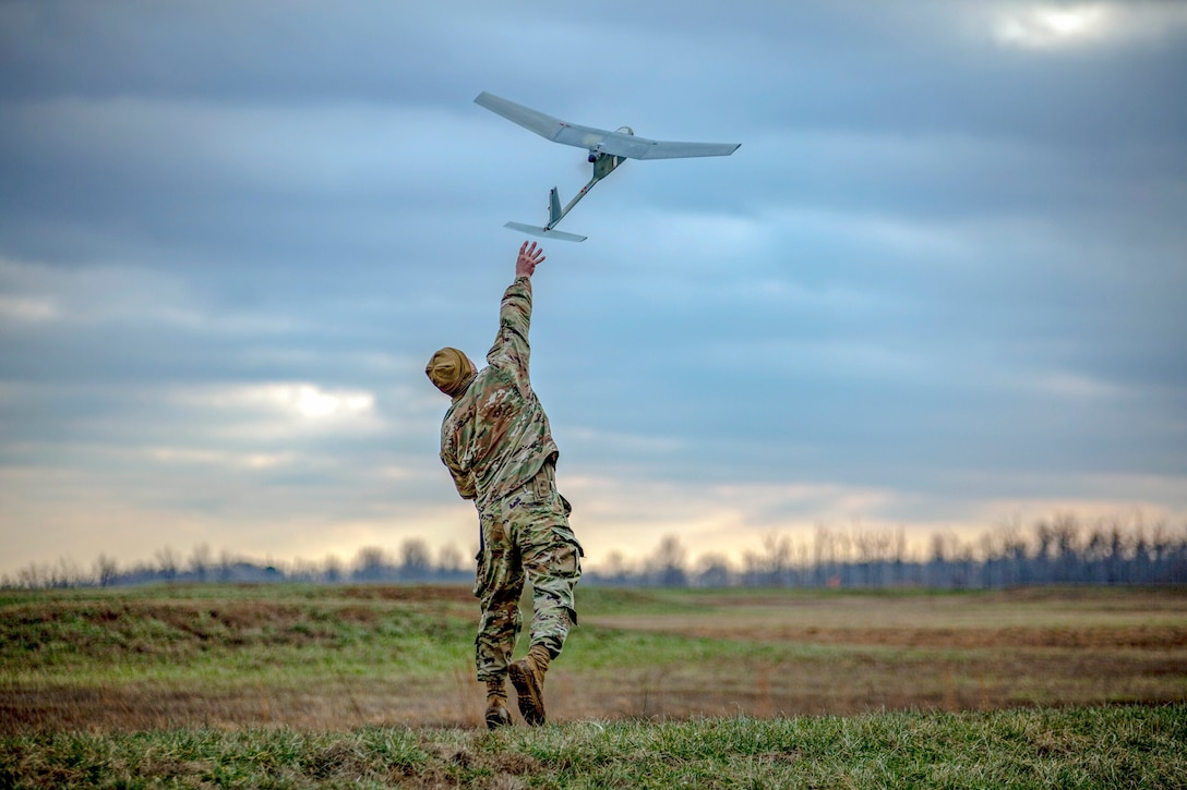 A soldier throws an unmanned aerial vehicle in a field.