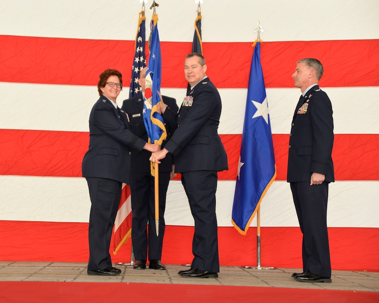 (Center) Col. Christopher McGraw, 136th Airlift Wing incoming commander, assumes command of the wing from Maj. Gen. Dawn Ferrell, Texas Air National Guard commander, during a change of command ceremony here January 26, 2019. McGraw comes to the wing after serving as director of operations, where he was responsible to the TANG commander on all matters pertaining to the direct operational planning, training, deployment and employment of more than 3,000 Airmen in three flying wings and five geographically separated units.
