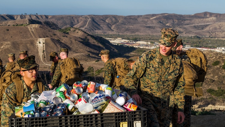 Marines with 1st Radio Battalion, I Marine Expeditionary Force Information Group, transport canned goods during a hike for those in need at Camp Pendleton, Calif., November 16, 2018.