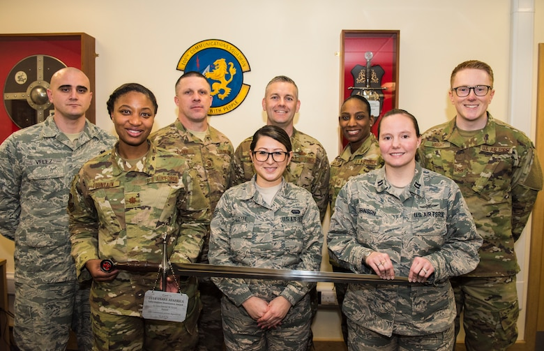 (First Row, From Left to Right) Maj. Erica Fountain (Commander), Senior Airman Aiko Little, Capt. Melissa Robinson, (Back Row, From Left to Right) Tech. Sgt. Ian Velez, Senior Master Sgt. Michael Miller, Chief Master Sgt. Jeremy Lindner, Senior Master Sgt. Lanora Waldron, and Staff Sgt. Matthew Wright, 100th Communications Squadron, pose with the Lt. Gen Harold W. Grant Award at RAF Mildenhall, Jan. 29, 2019. The Airmen were the squadron's top performers for 2018. (U.S. Air Force Photo by Senior Airmen Kelly O'Connor)