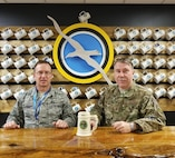 Master Sgts. Pat Ryan and Robert Segrin pose with Captain Paul L. Utz's stein, which was found after five decades during a building renovation project. Both Airmen were instrumental in the return of the stein to Utz's family.