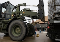 Tech. Sgt. Alfredo Cervantes, 375th Logistics Readiness Squadron NCO in charge of air transportation, guides Staff Sgt. Chance Sheek, 375th LRS ground transportation craftsman, as he operates a forklift carrying cargo during a mobility exercise, Jan. 23, 2019, at Scott Air Force Base, Illinois. Cervantes and Sheek were part of the Cargo Deployment Function, a team that ensures pallets are loaded onto an aircraft in a safe way that does not interfere with its center of gravity .