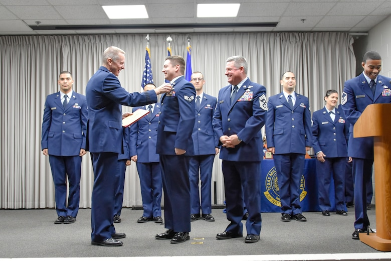 Maj. Gen. David McMinn, commander of the Texas Air National Guard, and Chief Master Sgt. Christopher Castle, command chief of the TANG, pin the Texas Medal of Merit on Senior Airman Kristopher Benfer, the 136th Airlift Wing Airman of the Year and Texas Air National Guard Outstanding Airman of the Year recipient, January 13, 2019 at Camp Mabry in Austin, Texas. Benfer will move forward to compete at the national level for the entire Air National Guard. (U.S. Air National Guard photo by Tech. Sgt. Katy Whitt)
