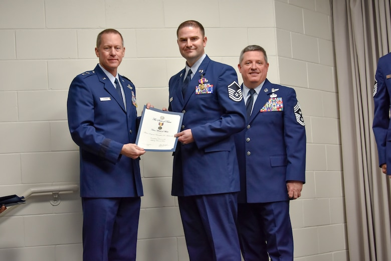 Master Sgt. Christopher Macharelli, 136th Maintenance Group quality assurance chief inspector, receives certificate from Maj. Gen. David McMinn, commander of the Texas Air National Guard, and Chief Master Sgt. Christopher Castle, command chief of the TANG, during the Outstanding Airman of the Year award ceremony January 13, 2019 at Camp Mabry in Austin, Texas. Macharelli was one of five Airmen chosen to compete from the 136th Airlift Wing. (U.S. Air National Guard photo by Tech. Sgt. Katy Whitt)