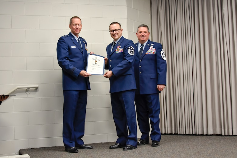 Master Sgt. Neil Robertson, 136th Maintenance Squadron first sergeant, receives a certificate and coin for his achievements from Maj. Gen. David McMinn, commander of the Texas Air National Guard, and Chief Master Sgt. Christopher Castle, command chief of the TANG, during the Outstanding Airman of the Year award ceremony January 13, 2019 at Camp Mabry in Austin, Texas. (U.S. Air National Guard photo by Tech. Sgt. Katy Whitt)
