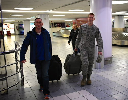 "932nd Airlift Wing staff members welcomed back several Airmen from temporary duties recently, including deployer Chaplain (Maj.) Michael Williams, at left. Shaking hands then helping carry his luggage upon arrival back in Illinois on January 29, 2019, is Maj. Luke Barker, the 932nd AW Director of Staff. The 932nd Airlift Wing is a 22nd Air Force unit, under Air Force Reserve Command.  The ""Gateway Wing"" unit is located at Scott Air Force Base, Illinois, not far from Saint Louis. (U.S. Air Force photo by Lt. Col Stan Paregien)"