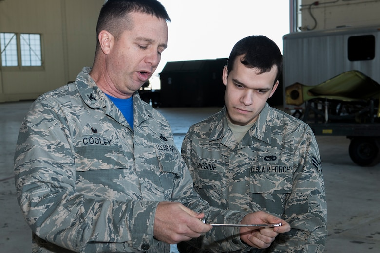"U.S. Air Force Reserve Col. Casey Cooley, 307th Maintenance Group commander, presents the ""Knuckle Buster"" award to Senior Airman Tyler Levesque on Jan. 25, 2019, Barksdale Air Force Base, Louisiana. Levesque is assigned to the 2nd Maintenance Squadron and received the award for discovering that two control cables (the Lateral Control cable and the Drag Chute cable) on a B-52H Stratofortress were improperly routed. His perserverance in ensuring the cables were correctly configured displayed his professionalism and dedication. (U.S. Air Force photo by Greg Steele)"
