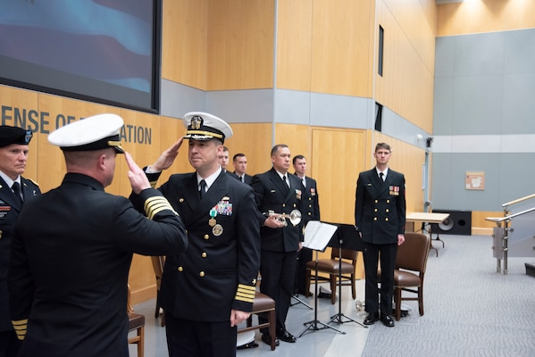 Capt. Joshua C. Himes, right, relinquishes command of the Defense Intelligence Agency Navy Element to Capt. Peter N. Shepard, left, during a change of command ceremony, Jan. 30, at the DIA headquarters on Joint Base Anacostia-Bolling.