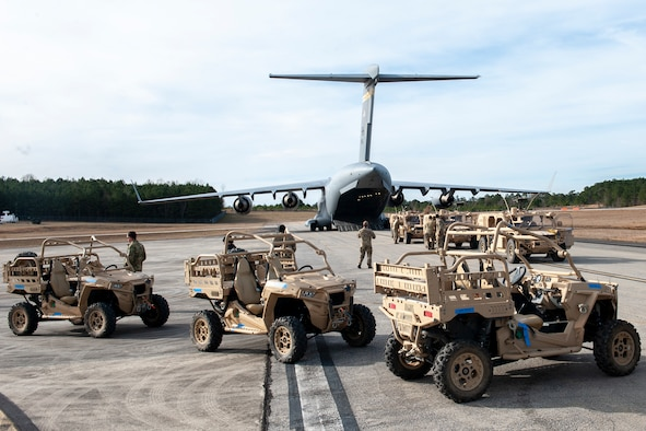 U.S. Army Soldiers and vehicles from the 3rd Special Forces Group prepare to board a Hawaii Air National Guard C-17 Globemaster III