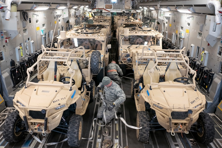 Members of the 164th Logistics Readiness Squadron secure U.S. Army vehicles onto a Hawaii Air National Guard C-17 Globemaster III