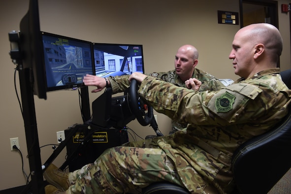 Two Airmen sit a three computer screens, one is sitting and using a steering wheel to control the drivng simulator on the screens.