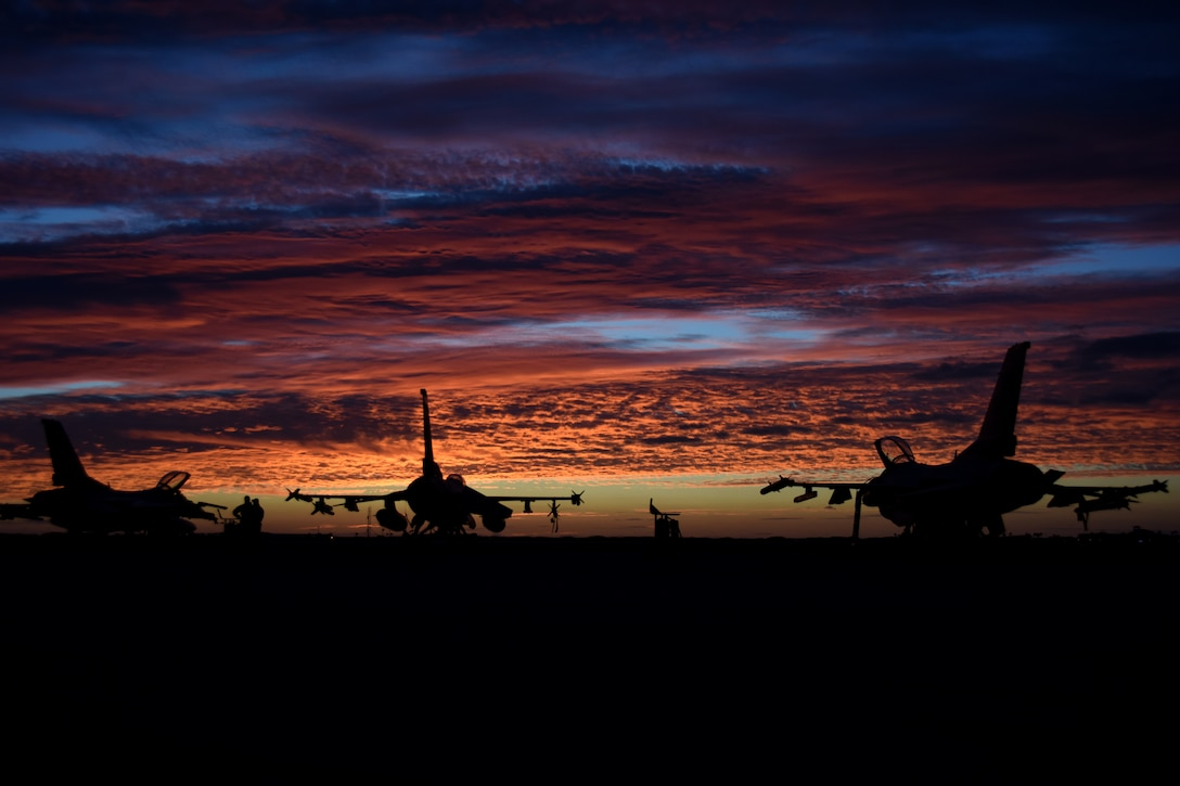 Military jets sitting on the tarmac are silhouetted against orange clouds of dawn.