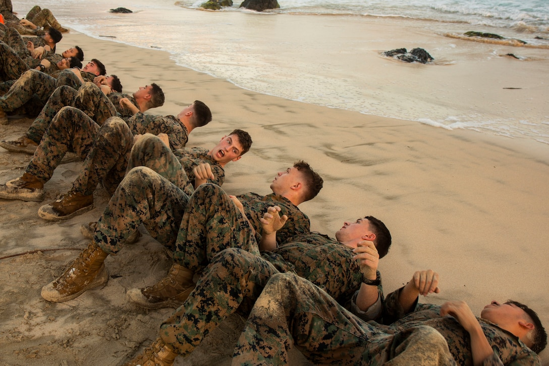 U.S. Marine Corps Lance Cpl. Matthew Cude (center) coordinates his squad as they endure a physical training exercise during the Advanced Infantry Marine Course (AIMC) on Marine Corps Base Hawaii, Jan. 28, 2019.