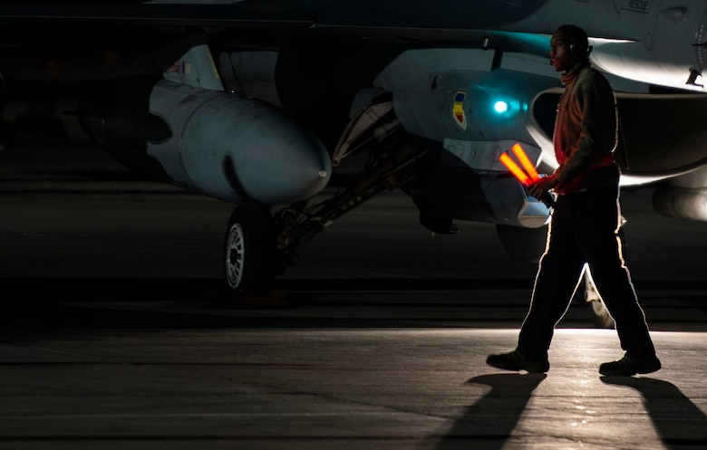 A U.S. Airman assigned to the 20th Aircraft Maintenance Squadron, 79th Aircraft Maintenance Unit, prepares to marshal an F-16CM Fighting Falcon during Exercise Red Flag 19-1 at Nellis Air Force Base, Nev., Jan. 30, 2019.