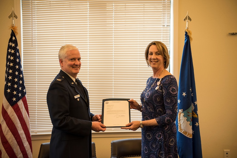 Kathy Edenborough, 628th Contracting Squadron director of business operations and 628th Air Base Wing small business specialist, receives her retirement certificate from Col. Dale Skinner, Air Force Life Cycle Management Center deputy director of contracting, during her retirement ceremony Jan. 30, 2019, at the Hunt Community Center on Joint Base Charleston, S.C.