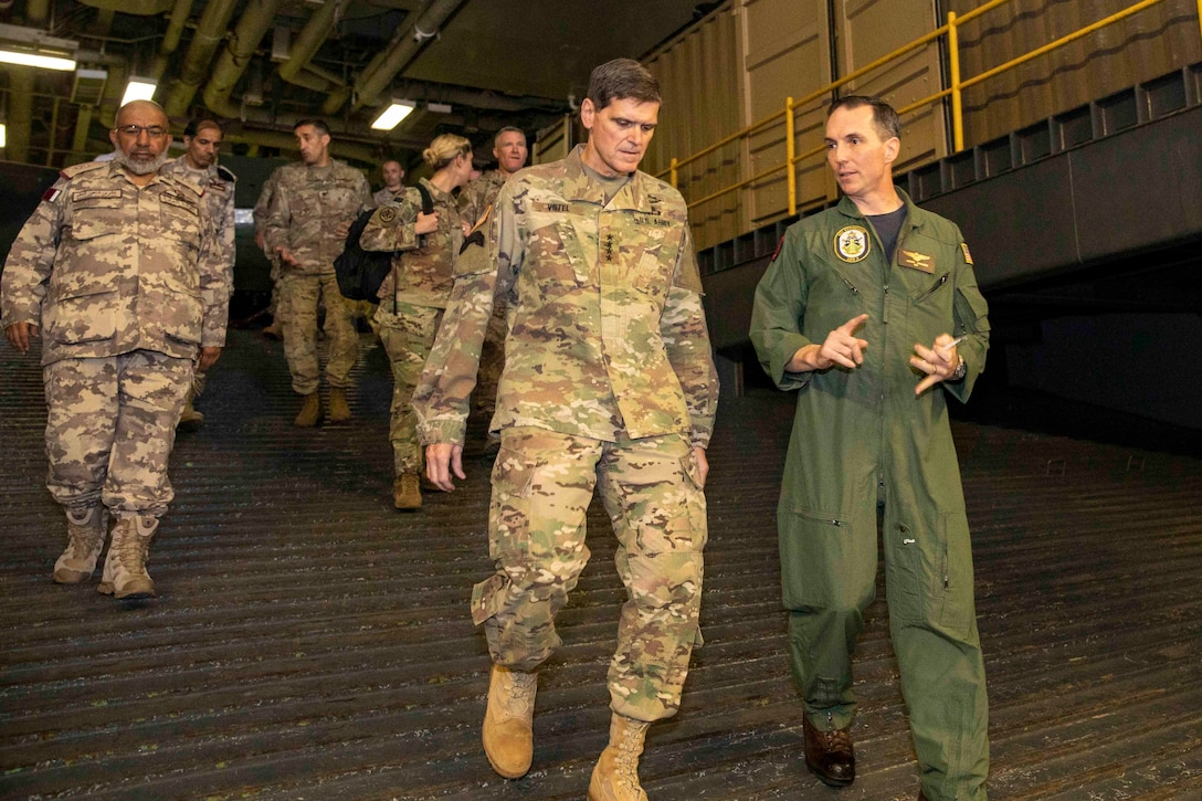Navy Capt. Jason Rimmer, right, commanding officer of the Wasp-class amphibious assault ship USS Kearsarge (LHD 3), discusses the capabilities of Kearsarge's well deck with Army Gen. Joseph L. Votel, center, Commander, U.S. Central Command. Kearsarge is the flagship for the Kearsarge Amphibious Ready Group and, with the embarked 22nd Marine Expeditionary Unit, is deployed to the U.S. 5th Fleet area of operations in support of naval operations to ensure maritime stability and security in the Central Region, connecting the Mediterranean and the Pacific through the western Indian Ocean and three strategic choke points. (U.S. Navy photo by Mass Communication Specialist 3rd Class Kaitlyn E. Eads/Released)