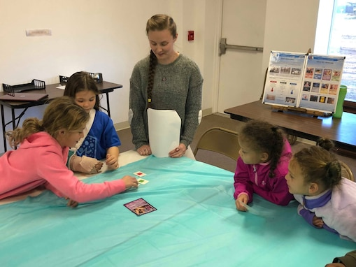 Naval Surface Warfare Center Panama City Division Scientist Myranda Chapman (center) observes students participating in a mock wargame between princesses and villains during a Girls Inc. science, technology, engineering, and mathematics outreach event Jan. 30, 2019. U.S. Navy photo by Katherine Mapp