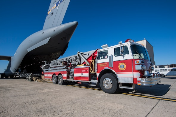 U.S. Airmen with the 305th Aerial Port Squadron and 732nd Airlift Squadron, guide a fire truck onto a C-17 on Joint Base Mcguire-Dix-Lakehurst, N.J., Jan. 31, 2019.