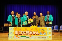 Visitors from Suo-Oshima present air station students with mikans