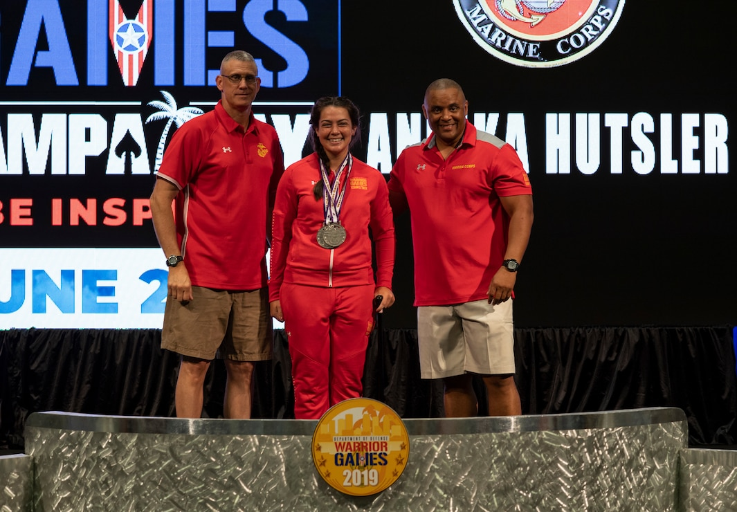 U.S. Marine Corps Lance Cpl. Annika Hutsler receives two silver medals for the 100m and 200m races in the DoD Warrior Games track competition at a medaling ceremony June 26, 2019. Col. Lawrence F. Miller (left), Commanding Officer of USMC Wounded Warrior Regiment, and Sergeant Maj. Edward Parsons, USMC Wounded Warrior Regiment Sergeant Major, presented the medals.  DoD Warrior Games were established in 2010 as a way to enhance the recovery and rehabilitation of wounded, ill or injured service members and veterans and to expose them to adaptive sports.